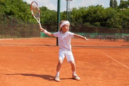 boy practicing tennis