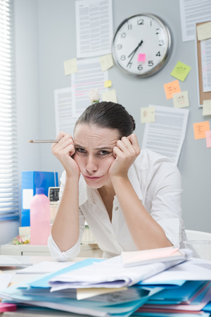 Photo pour Tired frustrated female office worker at desk looking at camera. - image libre de droit