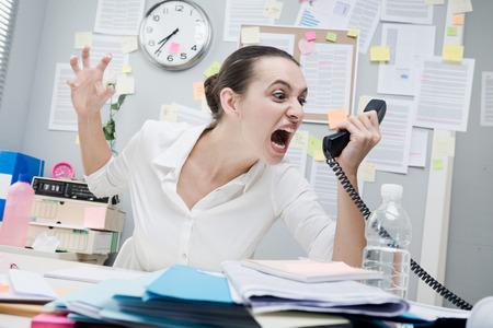Foto de Angry stressed businesswoman on the phone screaming out loud. - Imagen libre de derechos