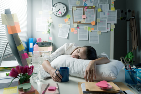 Photo pour Tired businesswoman at office desk waking up with pillow and coffee. - image libre de droit
