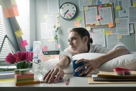 Foto de Overworked office woman with pillow working at computer. - Imagen libre de derechos