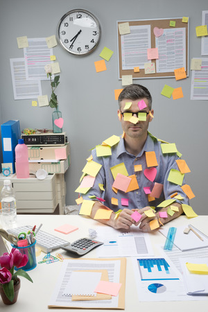 Photo for Busy white collar sitting at desk covered with stick notes. - Royalty Free Image