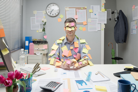 Photo pour Office worker sitting at desk covered with colorful post it stick notes. - image libre de droit