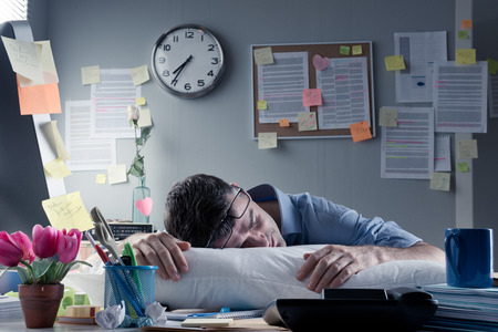 Photo pour Exhausted businessman sleeping at workplace with a pillow on his desk. - image libre de droit