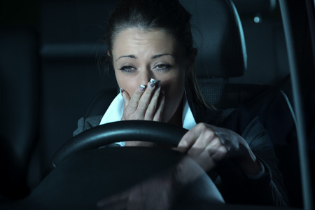Photo pour Distracted exhausted woman driving a car late at night. - image libre de droit