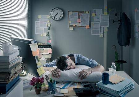 Foto de Exhausted businessman sleeping at workplace with a pillow on his desk. - Imagen libre de derechos