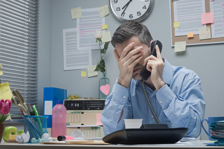 Photo pour Stressed employee on the phone touching his forehead. - image libre de droit