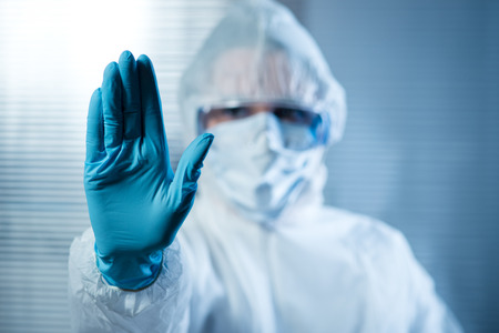Photo pour Scientist with hand raised in hazmat protective suit, stop concept. - image libre de droit