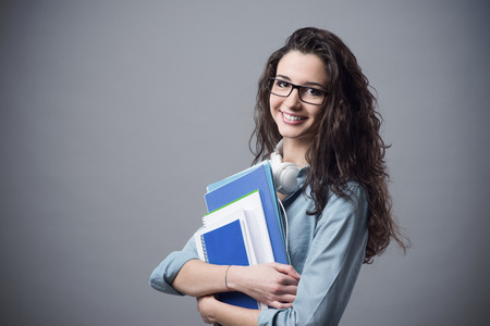 Photo pour Beautiful student girl posing with books and smiling at camera - image libre de droit