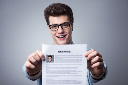 Foto de Young smiling man holding his resume applying for a job - Imagen libre de derechos