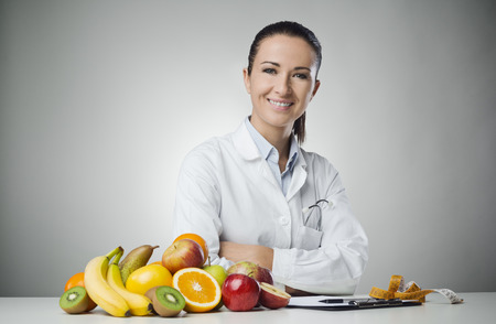 Foto de Confident nutritionist working at desk with fresh fruit - Imagen libre de derechos