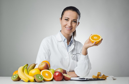 Photo for Smiling dietician sitting at desk and holding an orange - Royalty Free Image