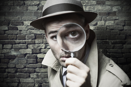 Photo pour Funny vintage detective looking through a magnifier - image libre de droit