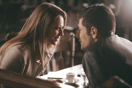 Foto de Romantic couple at the bar staring at each other's eyes - Imagen libre de derechos