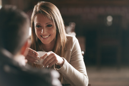 Photo pour Young couple at the bar having a coffee and flirting - image libre de droit