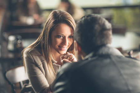 Foto de Romantic young couple dating and flirting at the bar, staring at each other's eyes - Imagen libre de derechos