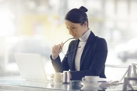 Foto de Busy elegant woman at the bar working on her computer next to a window - Imagen libre de derechos