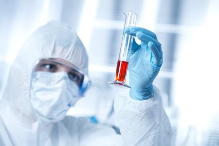 Foto de Researcher in hazmat protective suit examining a test tube in the chemical lab. - Imagen libre de derechos