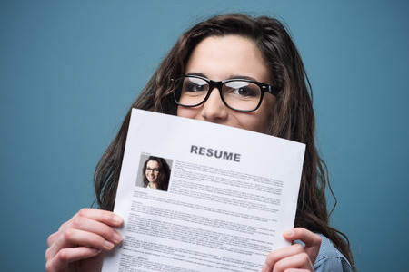 Photo for Young woman hiding behind her resume - Royalty Free Image