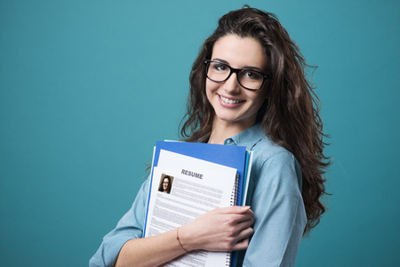 Foto de Young smiling cheerful woman holding her resume - Imagen libre de derechos