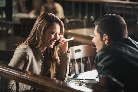 Photo pour Young cheerful man and woman dating and spending time together at the bar - image libre de droit
