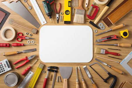 Photo pour DIY and home improvement banner with work and construction tools on a wooden workbench top view, blank white sign at center - image libre de droit