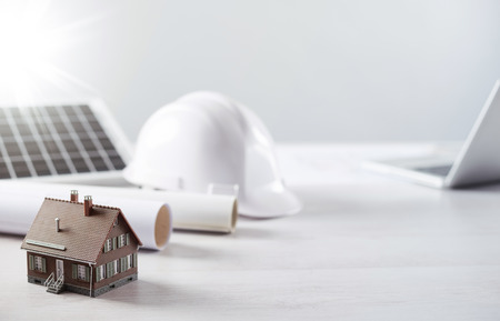 Photo for Structural engineer and architect desktop with safety helmet, solar panel and model house - Royalty Free Image