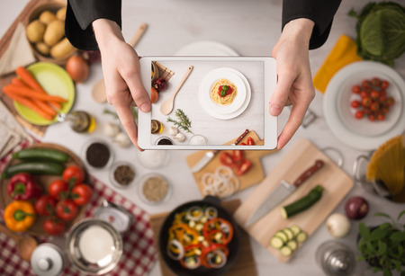 Foto de Cook\'s hands holding a touch screen tablet close up, kitchen table with food ingredients, vegetables and utensils  - Imagen libre de derechos