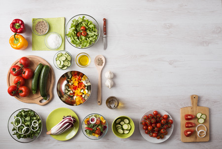 Healthy eating concept with fresh vegetables and salad bowls on kitchen wooden worktop, copy space at right, top view