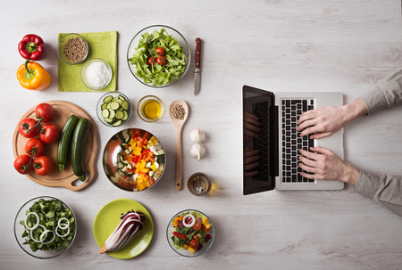 Photo for Man in the kitchen searching for recipes on his laptop with food ingredients and fresh vegetables on the left, top view - Royalty Free Image