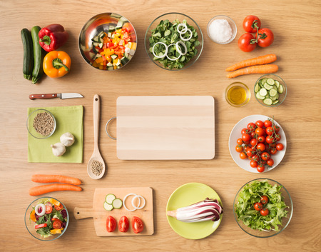 Foto de Creative vegetarian cooking at home concept with fresh healthy vegetables chopped, salads and kitchen wooden utensils, top view with copy space - Imagen libre de derechos