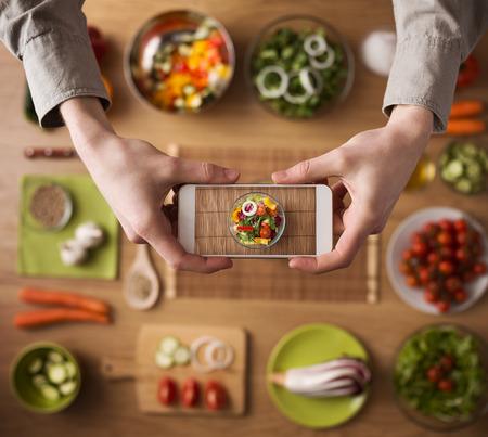 Foto de Man holding a smart phone hands close up, kitchen table worktop  - Imagen libre de derechos