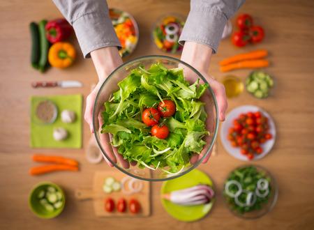 Photo pour Hands holding an healthy fresh vegetarian salad in a bowl, fresh raw vegetables  - image libre de droit