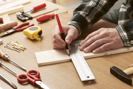 Photo pour Man working on a DIY project and measuring a wooden plank with work tools all around, hands close up - image libre de droit