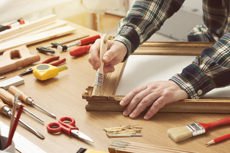 Photo pour Man varnishing a wooden frame hands close up with DIY tools on a work table - image libre de droit
