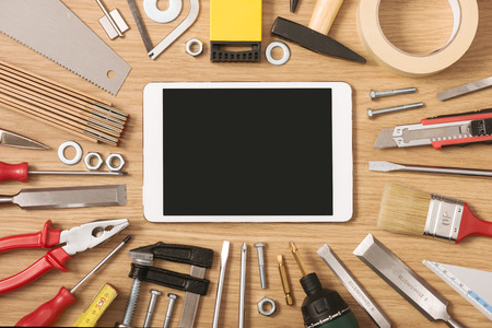 Foto de Digital touch screen banner with DIY and work tools all around on a wooden table, top view - Imagen libre de derechos