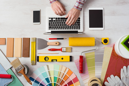 Photo for Professional decorator's hands working at his desk and typing on a laptop, color swatches, paint rollers and tools on work table, top view - Royalty Free Image