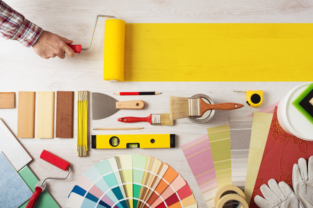Foto de Decorator holding a painting roller and painting a wooden surface, work tools and swatches at bottom, banner with copy space - Imagen libre de derechos