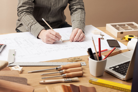 Photo pour Professional architect and construction engineer working at office desk hands close-up, he is drawing on a building draft with a pencil and a ruler - image libre de droit