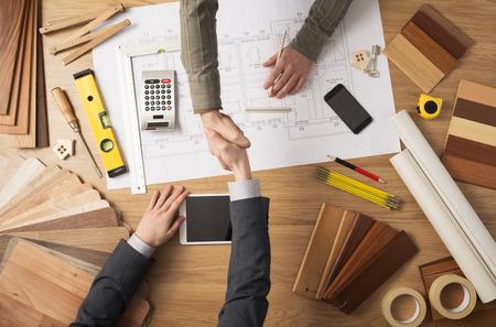 Foto de Architect and customer businessman shaking hands top view, desktop with building project, tools and wood swatches - Imagen libre de derechos