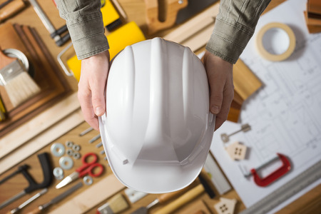Foto de Hands holding a protective safety helmet against a work table with hardware and construction tools, top view - Imagen libre de derechos