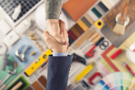 Photo for Businessmen shaking hands, construction and home renovation tools , top view - Royalty Free Image