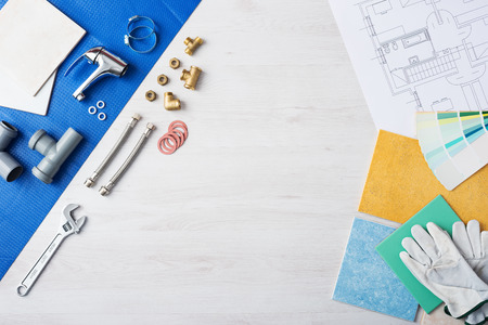 Foto de Plumber's work table banner with work tools, faucet, tiles and color swatches, top view, copy space at center - Imagen libre de derechos