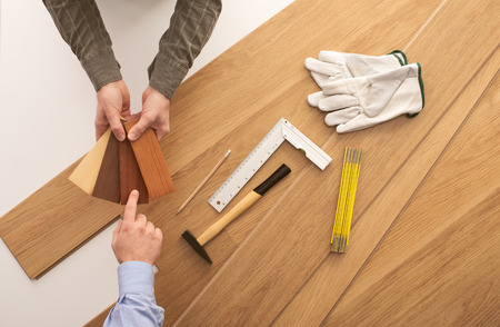 Photo for Carpenter showing some wooden baseboard swatches to a customer and choosing a color, flooring installation and work tools on background - Royalty Free Image