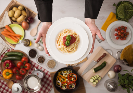 Foto de Professional chef's hands cooking pasta on a wooden worktop with vegetables, food ingredients and utensils, top view - Imagen libre de derechos