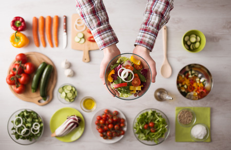 Photo for Man holding a fresh garden salad bowl with raw sliced vegetables, hands close up top view, ingredients and utensils  - Royalty Free Image