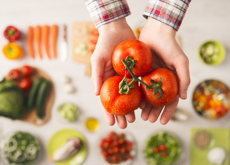 Photo pour Man holding fresh juicy tomatoes hands close up, vegetables and food ingredients, top view - image libre de droit
