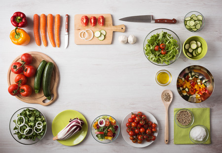 Photo pour Healthy eating concept with fresh vegetables and salad bowls on kitchen wooden worktop, copy space at center, top view - image libre de droit