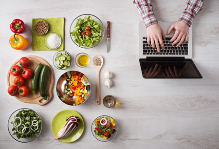 Photo pour Man in the kitchen searching for recipes on his laptop with food ingredients and fresh vegetables on the left, top view - image libre de droit