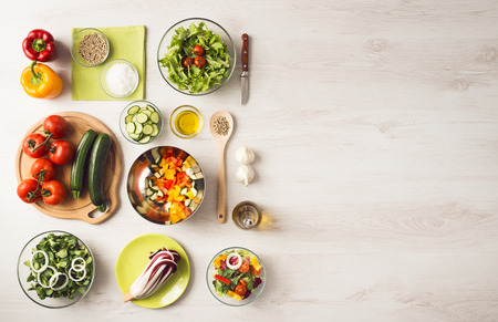 Photo pour Healthy eating concept with fresh vegetables and salad bowls on kitchen wooden worktop, copy space at right, top view - image libre de droit